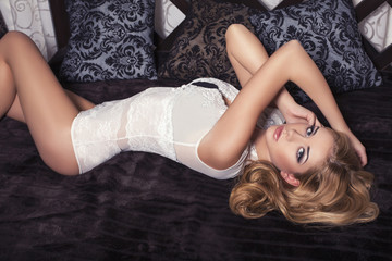 sexy woman with blond hair in lingerie lying on the bed