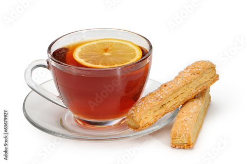 Glass cup with tea and a lemon on a glass saucer and cookies.