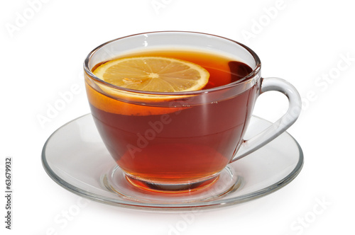 Glass cup with tea and a lemon on a glass saucer