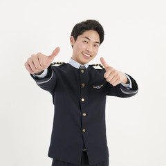 Cheerful airline pilot wearing uniform with thumb up