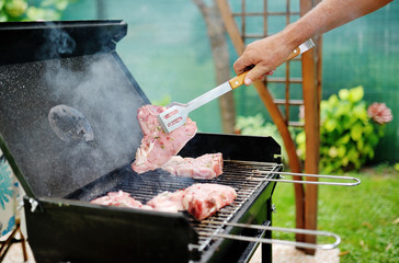 Man at a barbecue grill preparing meat for a garden party