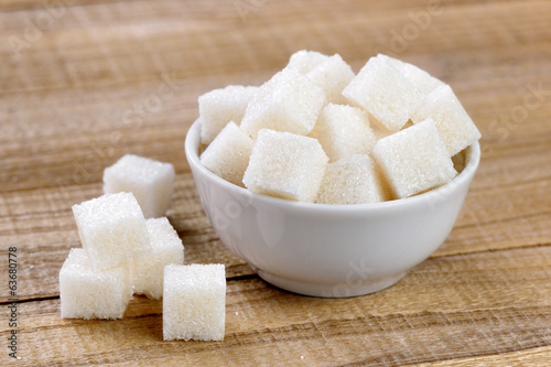 Sugar cubes in bowl on wooden table