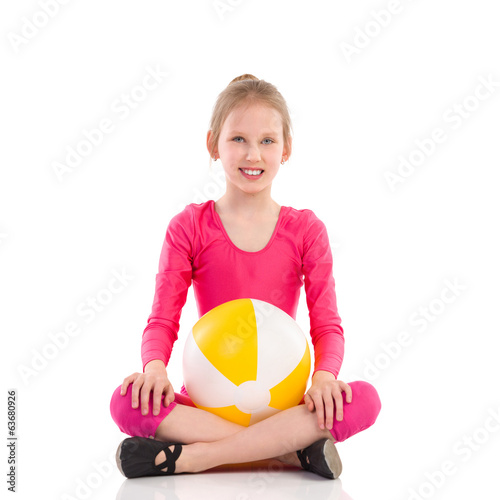 Smiling young girl posing with a ball