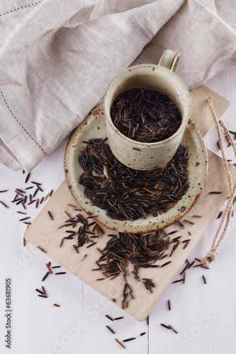 Black wild rice in a ceramic plate on a white wooden background