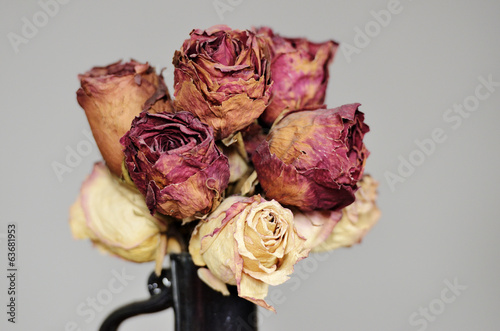 bouquet of dried roses in ceramic vase