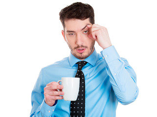 Tired, stressed, sleepy young business man holding cup coffee