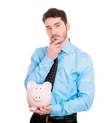 To save or spend? Business man holding piggy bank, thinking