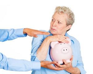 Don't steal my savings. Senior woman protecting piggy bank