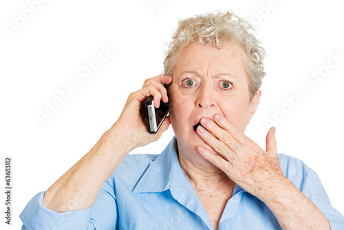 Old shocked lady receiving bad news on mobile phone