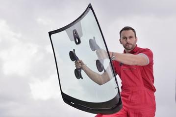 mechanic holding windshield