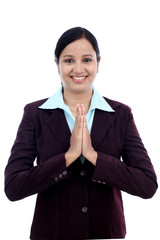 "Smiling young business woman greeting ""Namasthe"""