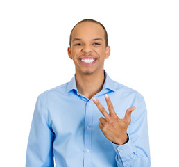 Smiling man giving a three sign