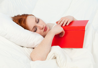 young woman reading in her bed, white background