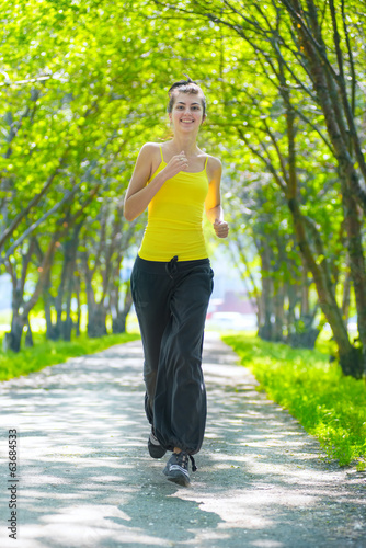 Runner - woman running outdoors in green park