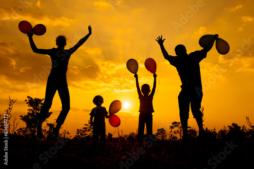 Happy  family playing with balloons on the  road in the  sunset