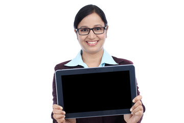 Smiling young business woman showing tablet computer