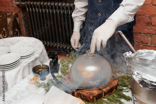 Chef is smoking a dish before serving