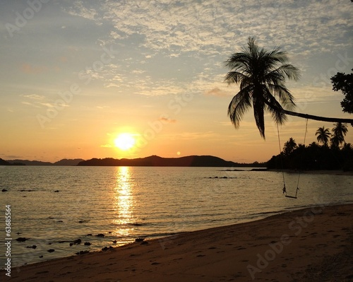 tropical sunset with coconut tree on the sand beach