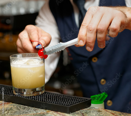 Bartender is decorating cocktail with cherry