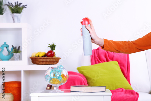 Sprayed air freshener in hand on home interior background