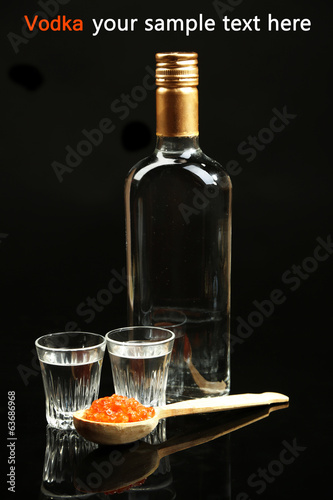 Bottle of vodka, red caviar  isolated on black