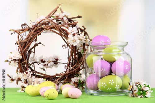 Composition with Easter eggs in glass jar and decorative wreath