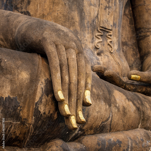 Hand of an ancient Buddha statue in the temple of Sukhothai Hist