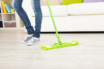 Woman with mop cleaning wooden floor from dust