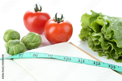 Book with measuring tape and vegetables isolated on white
