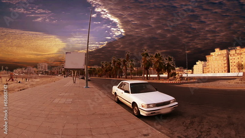 Street in the city of Jeddah with palm trees at sunset