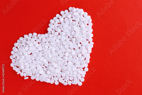 Heart of pills on red background