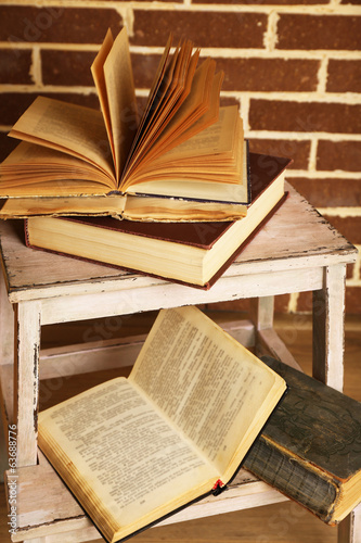 Books on wooden ladder on  color wall background
