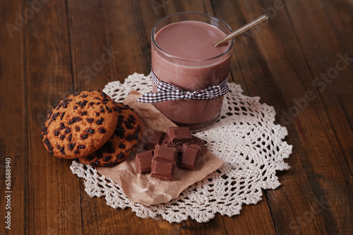 Chocolate milk in glass, on wooden table background