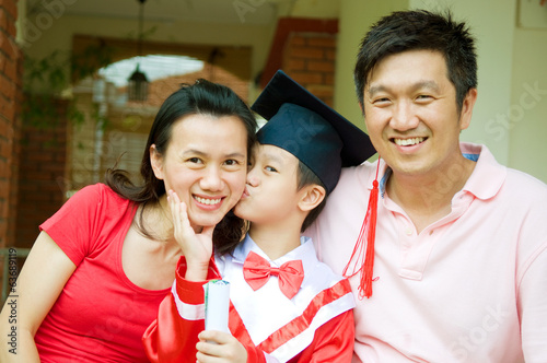 Asian kid kiss his mother on kinder graduation day