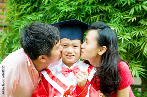 Asian parent kiss their son on his kinder graduation day.