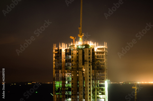 cranes build large buildings at night
