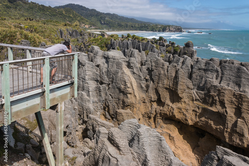 man taking pictures of Pancake rocks at Punakaiki