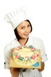 chef holding a tray of cakes