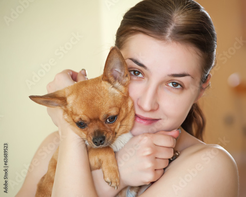Happy girl with chihuahua dog in arms.