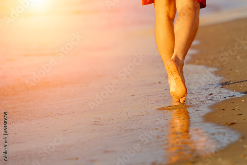 Running legs of runner on beach