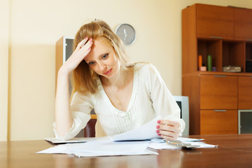 Sad woman reading financial documents