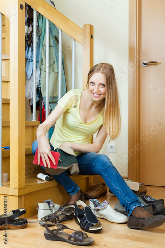Happy blonde woman cleaning footwear