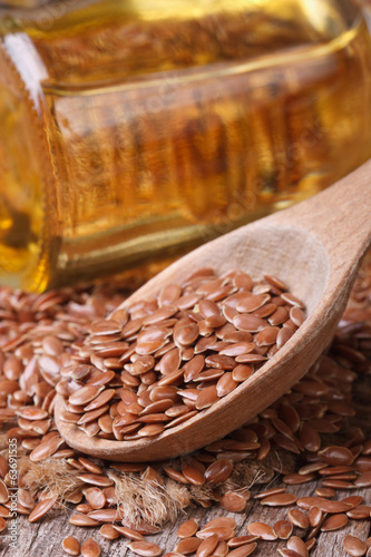 Flax seed in a wooden spoon and the bottle with oil