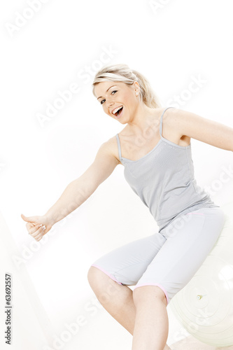 young woman with a ball at gym