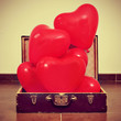 heart-shaped balloons in an old suitcase