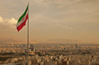 Leinwanddruck Bild - Iran Flag in the Wind Above Skyline of Tehran