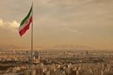 Fototapety Iran Flag in the Wind Above Skyline of Tehran
