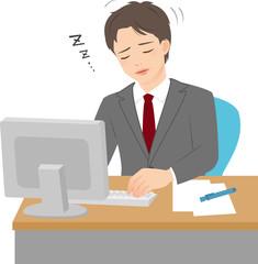 職場のデスクで居眠りするビジネスマン