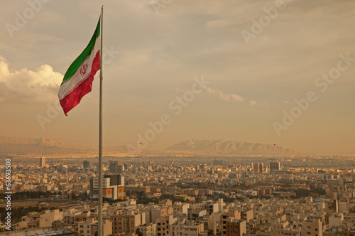 Iran Flag in the Wind Above Skyline of Tehran