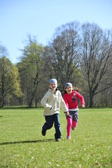 Boy and girl are running on the grass